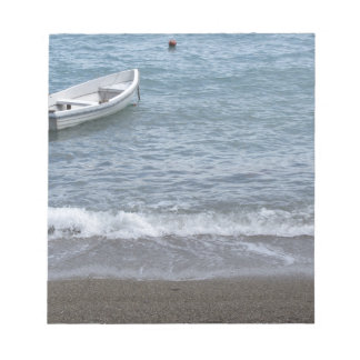 Single rowing boat moored in a harbor on the sea notepad