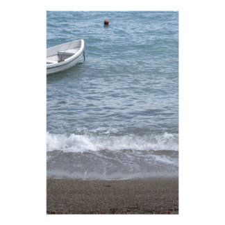 Single rowing boat moored in a harbor on the sea stationery