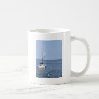 Single sailboat lies at anchor in a harbor coffee mug