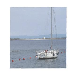 Single sailboat lies at anchor in a harbor notepad