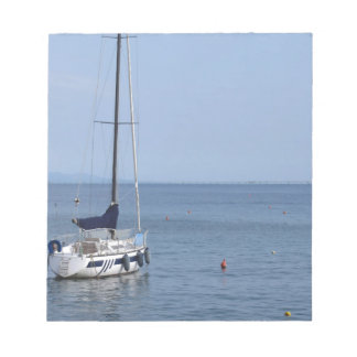 Single sailboat lies at anchor in a harbor notepads