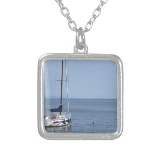 Single sailboat lies at anchor in a harbor silver plated necklace