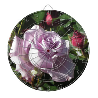 Single violet rose flower with red roses around dartboard