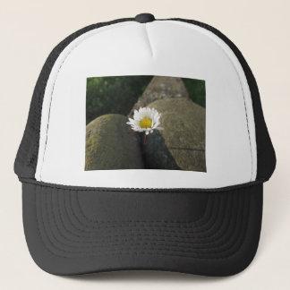 Single white daisy flower between the stones trucker hat