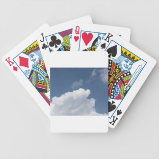 Sky with giants clouds and sun rays through bicycle playing cards