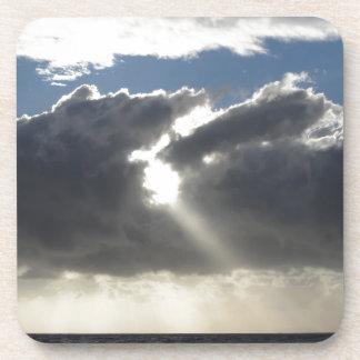 Sky with giants cumulonimbus clouds and sun rays coaster