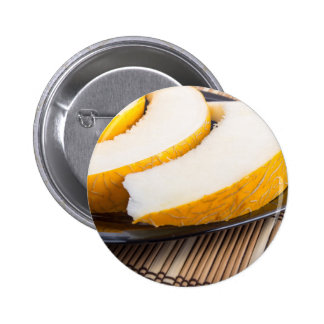 Slices of juicy yellow melon on a black plate 2 inch round button