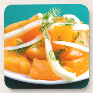 Slices of orange tomato on a plate with onions beverage coasters