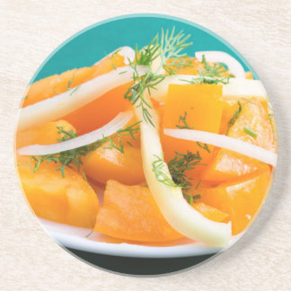 Slices of orange tomato on a plate with onions drink coaster