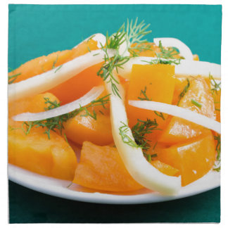 Slices of orange tomato on a plate with onions napkin