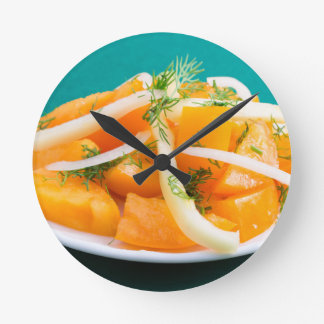 Slices of orange tomato on a plate with onions round clock