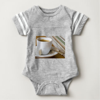 Small cup of espresso on a saucer with sugar baby bodysuit
