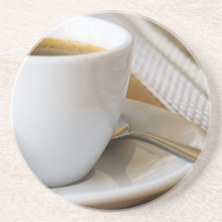 Small cup of espresso on a saucer with sugar coaster