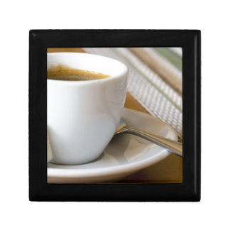 Small cup of espresso on a saucer with sugar gift box