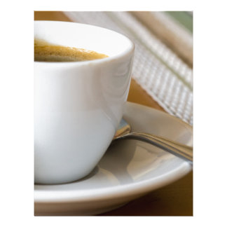 Small cup of espresso on a saucer with sugar letterhead