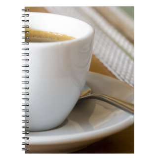 Small cup of espresso on a saucer with sugar notebook