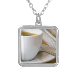 Small cup of espresso on a saucer with sugar silver plated necklace