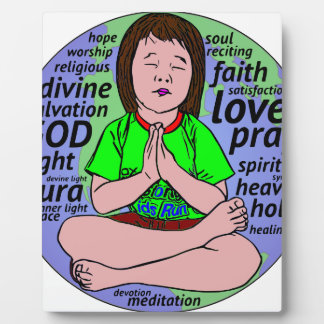 Small girl praying and meditating,sitting on earth plaque