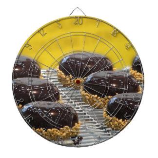 Small glazed chocolate cakes with hazelnut grains dartboard