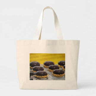 Small glazed chocolate cakes with hazelnut grains large tote bag