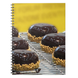 Small glazed chocolate cakes with hazelnut grains notebook