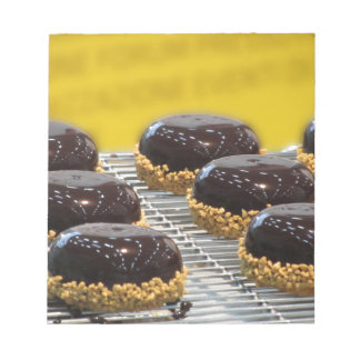 Small glazed chocolate cakes with hazelnut grains notepad
