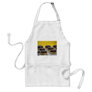 Small glazed chocolate cakes with hazelnut grains standard apron