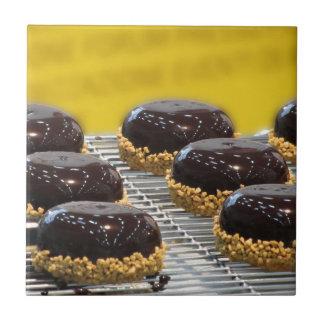Small glazed chocolate cakes with hazelnut grains tile