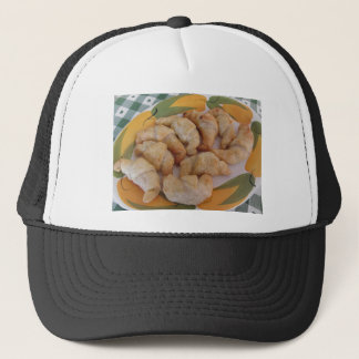 Small homemade salty croissants with sausage trucker hat