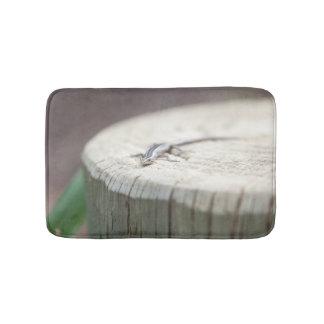 Small lizard on a wooden stump bath mat
