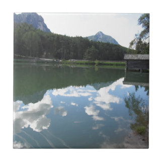 Small mountain lake with reflections of clouds tile
