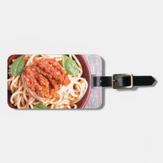 Small portion of cooked spaghetti with tomato luggage tag