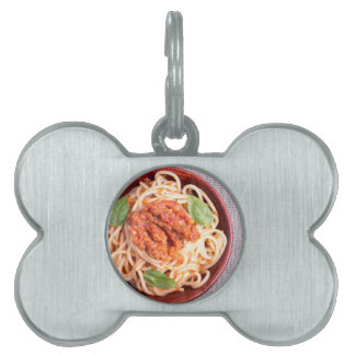 Small portion of cooked spaghetti with tomato pet name tag