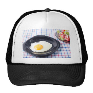 Small portion of the breakfast of fried egg trucker hat