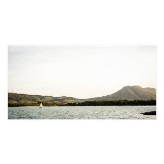 Small ship sailing on a lake at the afternoon card