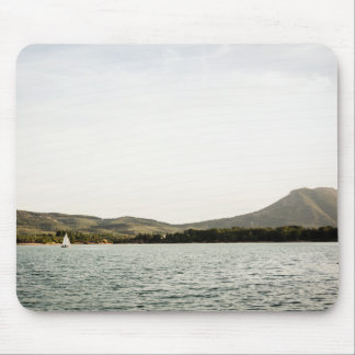 Small ship sailing on a lake at the afternoon mouse pad