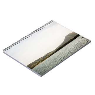 Small ship sailing on a lake at the afternoon notebook
