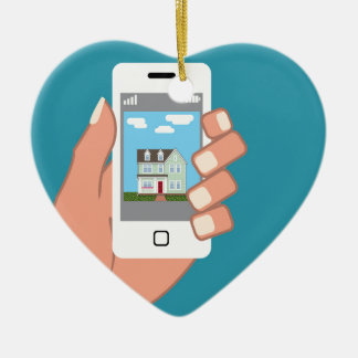 Smartphone in hand with house picture ceramic heart ornament