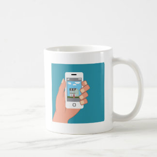 Smartphone in hand with house picture classic white coffee mug