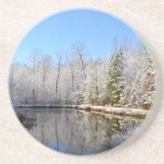 Snow covered landscape around the pond drink coaster