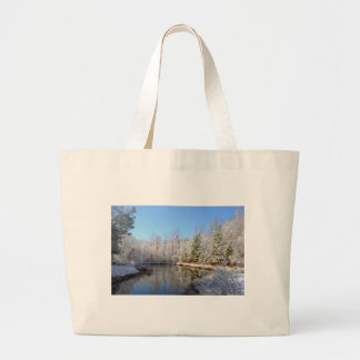 Snow covered landscape around the pond large tote bag