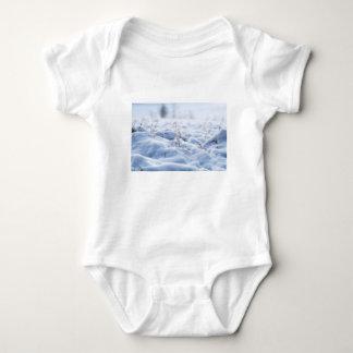 Snow on a meadow in winter macro baby bodysuit