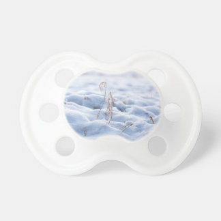 Snow on a meadow in winter macro pacifier