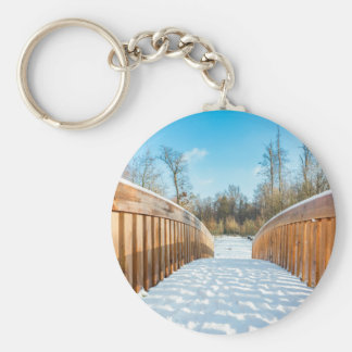 Snow on wooden bridge in forest basic round button keychain