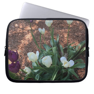 Snow white tulip type flowers in a garden laptop sleeve