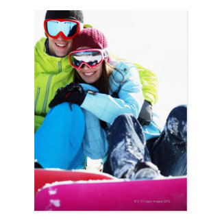 Snowboarder couple sitting on snow postcard