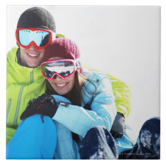 Snowboarder couple sitting on snow tiles