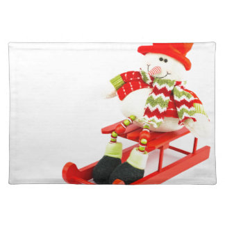 Snowman figurine sitting on red sledge placemat
