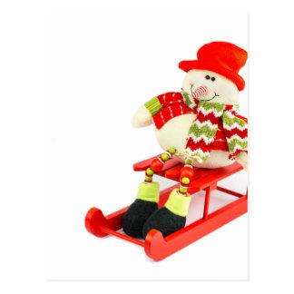 Snowman figurine sitting on red sledge postcard