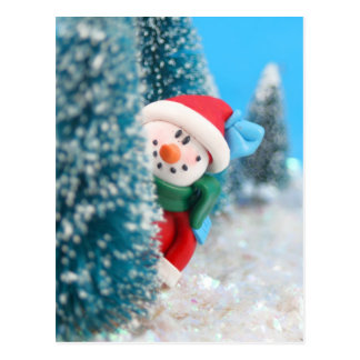 Snowman hiding or peeking from behind a tree postcard